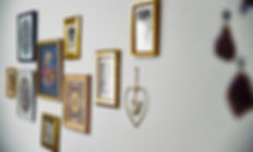קיר גלריה של תמונות אישיות במסגרות זהב.