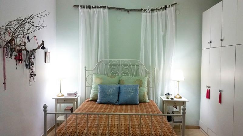 המיטה היא מרכז החדר, מאחוריה קיר צבוע מנטה