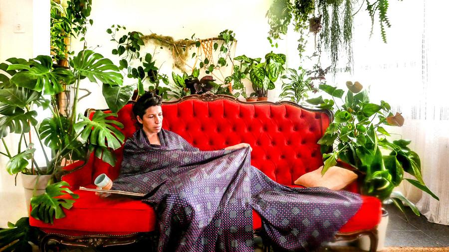 רינת טל על הספה הכתומה בבית בתוך ג'ונגל של עציצים