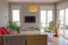 מבט אל הסלון מכיוון פינת האוכל, ספת מרבץ מרווחת ונוף נשקף מהחלונות. צילום ינאי מנחם..