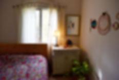 מבט על חדר השינה. שידת וינטג' מתפקדת על תקן של שידת צד, מראה וחישוקי ריקמה