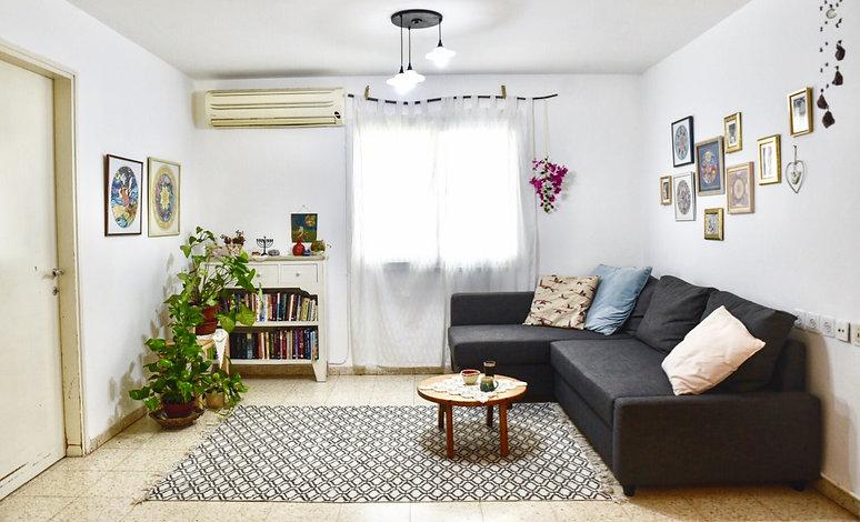 מבט אל הסלון שרוהט בפשטות. ספה פינתית, שטיח ווילונות לבנים. ומעל הספה קיר תמונות אישיות.