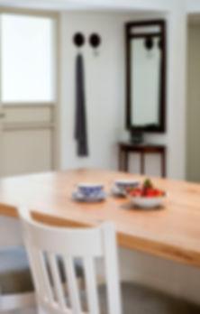 מבט מהאי אל הכניסה לבית. על האי כוסות פוצלן כחולות ותותים.