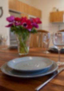 השולחן ערוך. כלי קרמיקה כחולים וזר כלניות פורח.