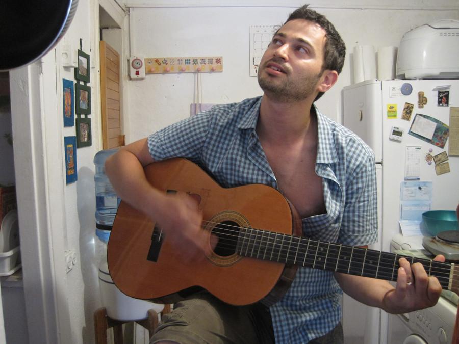 בן הזוג של רינת מנגן בגיטרה בין המטבח למקלחת בדירה בגורדון.