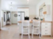 מבט אל המטבח מכיוון האי ופינת האוכל. מטבח לבן ומואר.