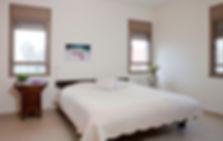מבט אל חדר שינה הורים, שידות צד שונות זו מזו ומצעים לבנים.