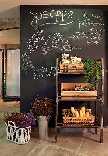 קיר הספיישלים של המסעדה. שידת ברזל, ארגזי עץ על רקע קיר לוח גיר צבוע בשחור.