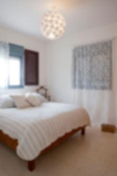 חדר שינה הורים. מנורה מקיפולי נייר אוריגמי מעל המיטה.