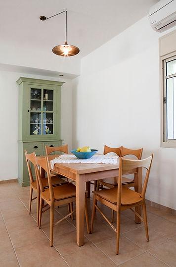 מבט אל פינת האוכל. סט שולחן וכסאות משנות ה80 ושידת ויטרינה בסגנון כפרי.