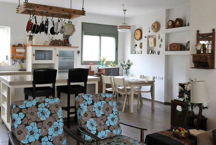 מבט מהסלון אל פינת האוכל והמטבח. רהיטי ונטג' מופצים ואוסף שעונים.