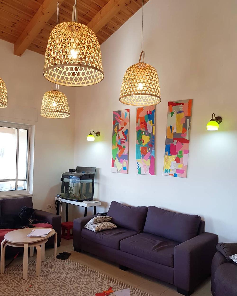 התמונות המוכנות תלויות בסלון. על קיר גבוהה וברקע אהילים מבמקוק
