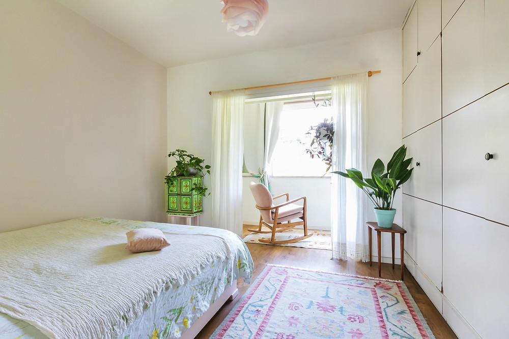 חדר שינה בעיצוב דיקלה מנחם. פרטי וינטג' עדינים וכורסה ורודה מול החלון.