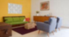 הסלון. קיר צהוב מרשים בשילוב משרביות ורהיטי וינטג' משופצים.