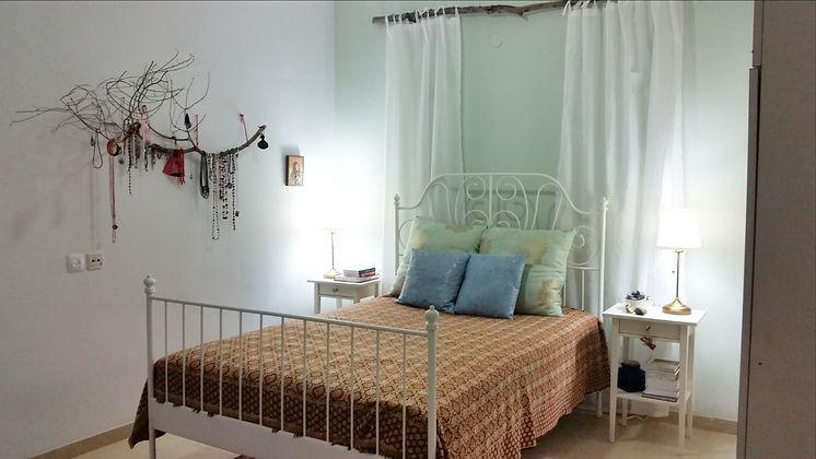 סטיילינג לחדר שינה. קיר בגוון מנטה וענף כמתלה תכשטים