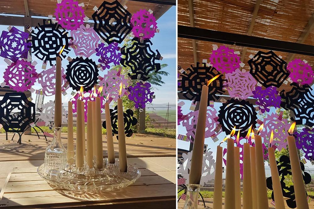 הנרות דולקים על רקע החלון המקושט במיגזרות נייר