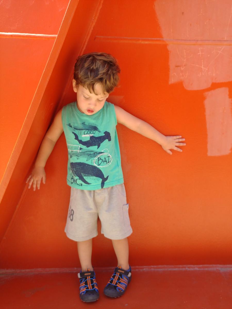 ילד מתוק באופן מיוחד עומד על רקע קיר כתום