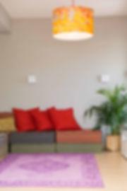 צבעוניות חזקה בסלון. שטיח סגול ומעליו מנורה כתומה