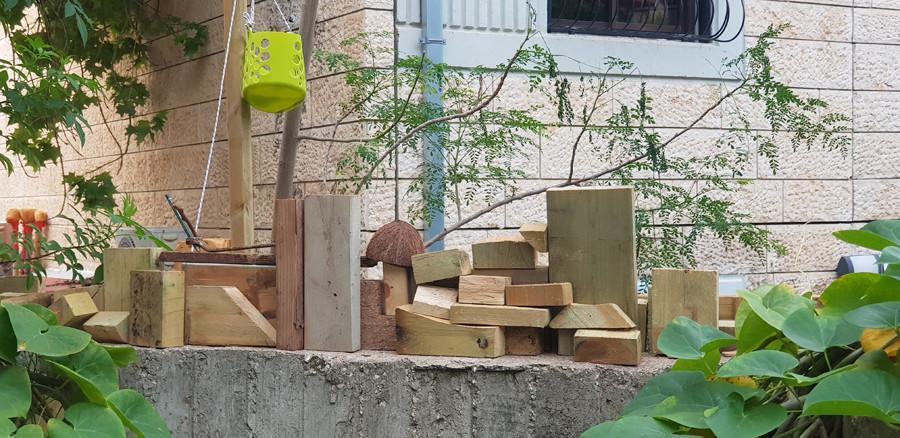 פינת עבודה בגינה. קוביות עץ לבנייה ומשחק.