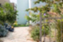 מבט אל הכניסה לבית, חצר פורחת ומזמינה. צילום ינאי מנחם.