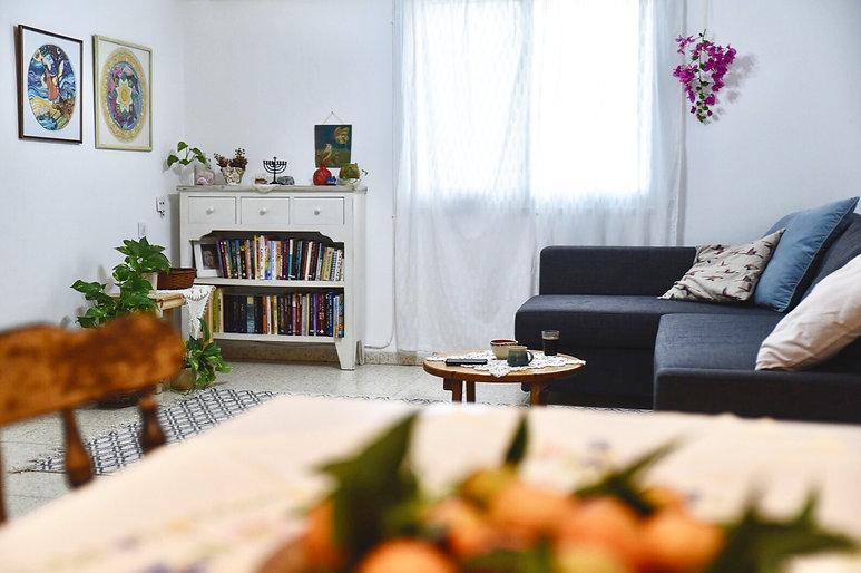 .בסלון, שידת וינטג' לבנה משמשת כספריה ותמונות ממוסגרות של בעלת הבית.