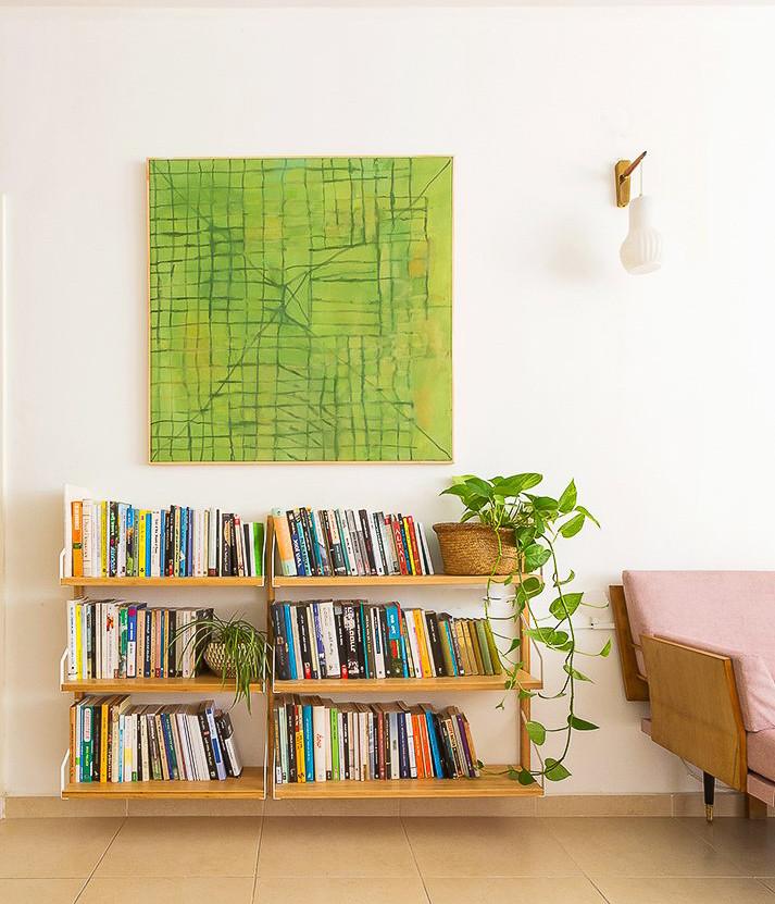 ספרייה ומעליה תמונה בגווני ירוק פרט בעיצובה של דקלה מנחם