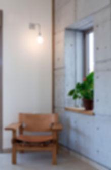 פרט חלון בולט בקיר בטון חשוף וכורסת עץ ועור.