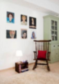 פינת קריאה בין פינת האוכל לבין הסלון. כיסא נדנדה מעץ ודיוקנאות שציירה בעלת הבית.