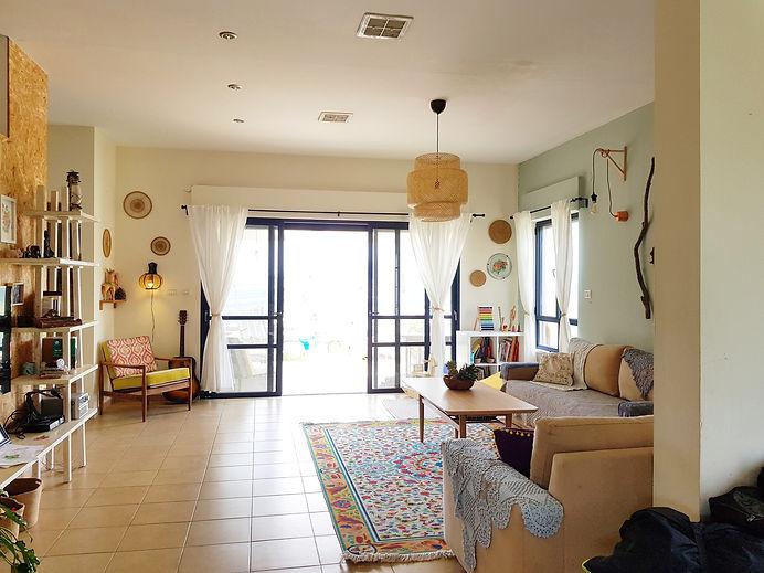 מבט על הסלון מכייון הכניסה. רואים את החלון הגדול  השמקיף למרפת ואת פינת הישיבה.