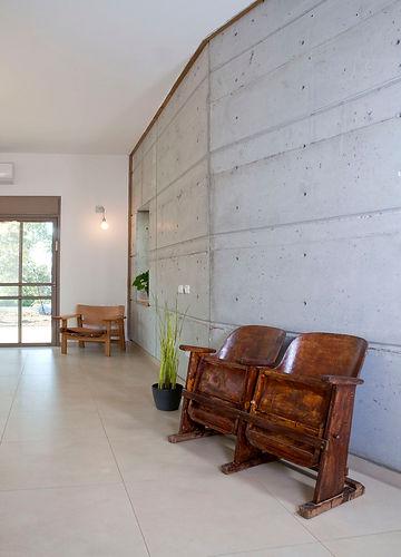 כסאות קולנוע ישנים על רקע קיר בטון חשוף.