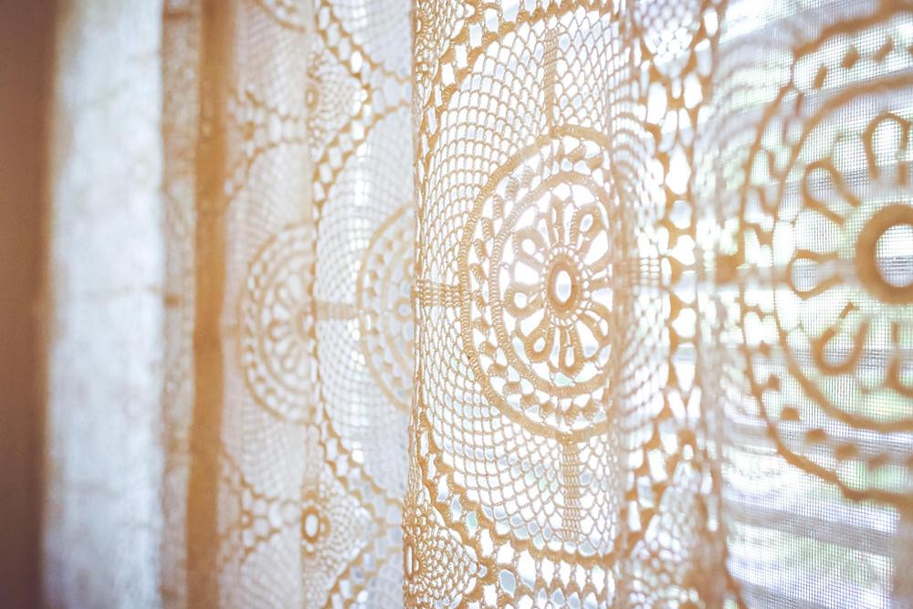 פרט של כיסוי מיטה שהפך לווילון. בד קרושה רקום ועדין בצבע שמנת.