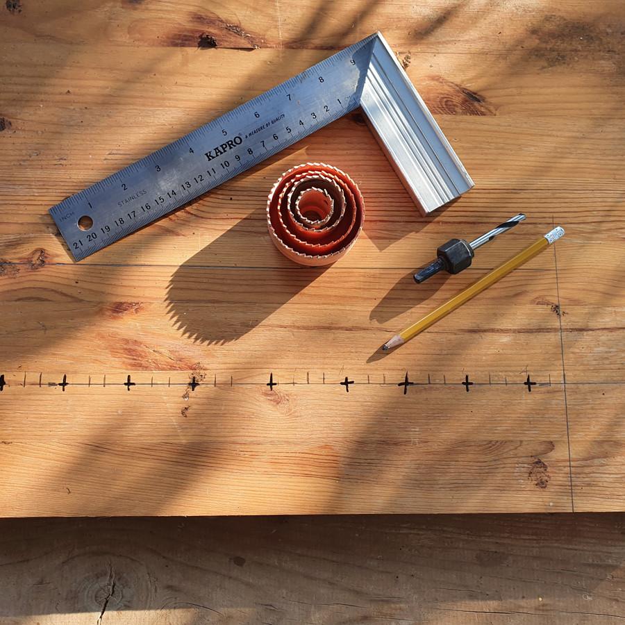 חלק ממה שצריך כדי להכין חנוכייה מלוח עץ. מקדחה וסט מקדחי כוס, סרגל ועיפרון