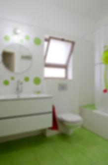 מבט אל חדר רחצה ילדים. רצפה ירוקה ווליון אמבט עם ציור צפרדעים.
