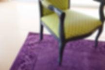 פרט מיוחד בסלון, שטיח סגול וכורסת וינטג' מחודשת באפור וירוק
