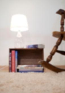 פרט בפינת הקריאה. רגל כיסא הנדנדה וארגז לספרים.