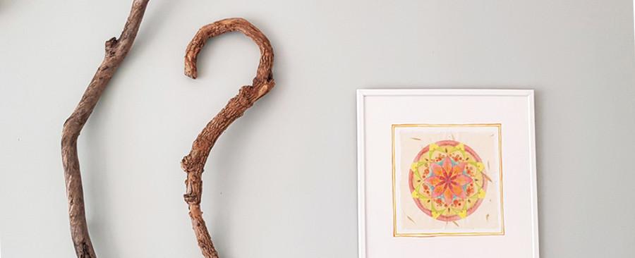 פרט מתוך עיצוב לקיר הסלון. מנדלה וענפים תלויים על קיר צבוע בצבע מנטה.