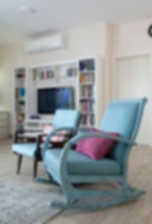 פינה בסלון. קיר הטלויזיה ושתי כורסאות משופצות צילום הגר דופלט..