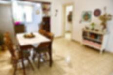 מבט מפינת האוכל אל הכניסה לבית. ריקמות ממוסגרות וחפצי כוח מקשטים את הקירות