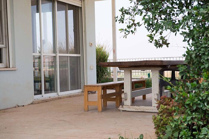פרט בפרגולה. שולחן נגרים ישן וספסלי עץ