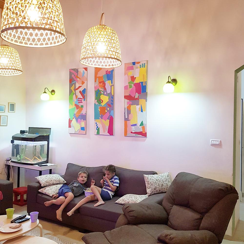יושבים לנוח ומנשנים פופקורן ברקע תמונות צבעוניות ומנורות קיר צבעוניות