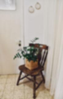 פינה במבואה. כיסא עץ ישן ועליו עציץ ירקו. ברקע ווילון תחרה וחישוקי ריקמה