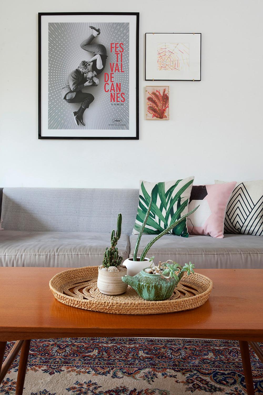 פרט בעיצוב של דיקלה מנחם. ספה עליה כריות נוי בהדפסים שונים, על שולחן הסלון כלי קרמיקה עם סקולנטים.