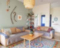הסלון. ספות בגווני כחול אפור, קיר מנטה. מנדלה וענפים מקשטים את הקיר ואהיל קש גדול.