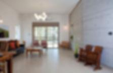 מבט מהכניסה אל הסלון. קיר בטון חשוף מלווה את החלל לכל אורכו.