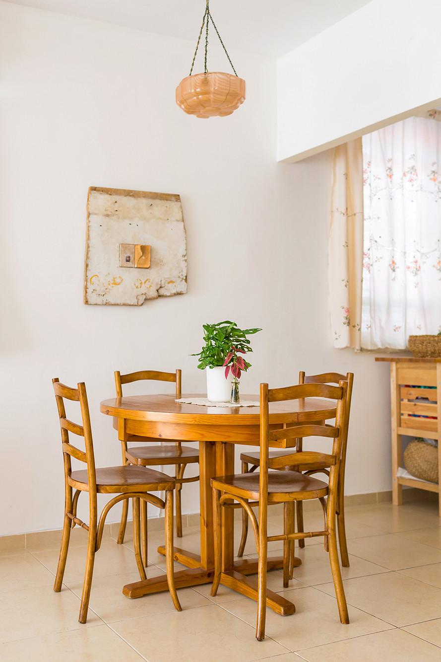 פרט בעיצובה של דקלה מנחם פינת אוכל מעץ מלא ומעליה מנורת זכוכית וינטג' ורודה. על הקיר עבודת אמנות מיוחדת.