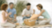 Two adult couples in their mid 40's having a picnic on the beach. They are business owners and happy that they have a life insurance retirement plan provided by InsuranceQuotesPro.us