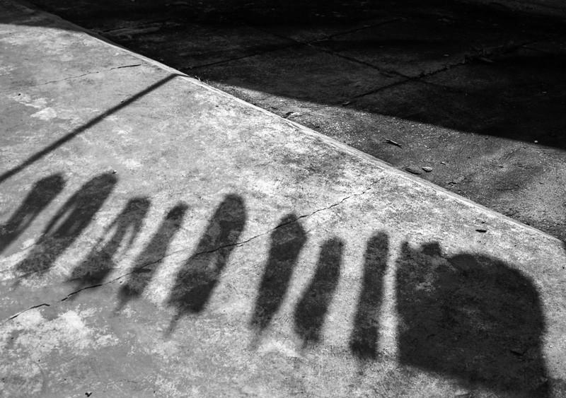 Sombra de varal de roupas em piso de cimento.