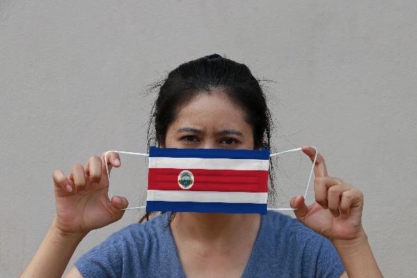 Mujer sostiene su mascarilla frente al rostro. La mascarilla tiene la bandera de Costa Rica.