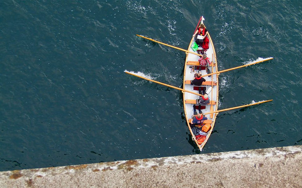 "The St. Ayles Skiff is a 4 oared rowing boat, designed by Iain Oughtred and inspired by the traditional Fair Isle skiff. The boat's hull and frames are built using clinker plywood and it measures 22' with a beam of 5' 8"". It is normally crewed by four sweep rowers with a coxswain."