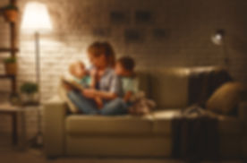 Family before going to bed mother reads children a book about a lamp in the evening_